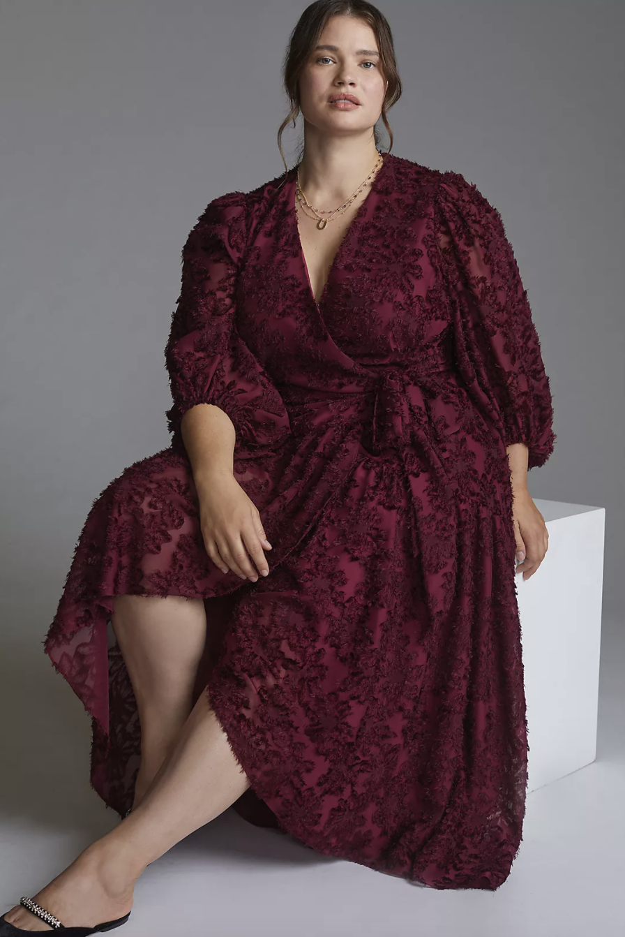 plus size white model with brown hair sitting in burgundy red wrap dress