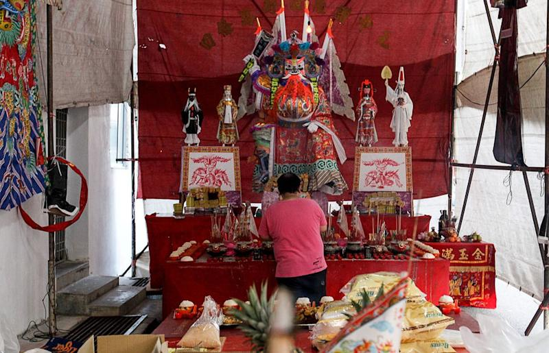 A man offers prayers to the giant paper-made deity called 'Tai Su Yah', the God of Hell before the start of the Teochew puppet show at Lebuh Tye Sin in George Town, August 21, 2018.