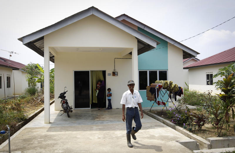 In this photo taken on Oct. 4, 2012, Faizal Zulkifli leaves his house after lunch at a rural community in Pulau Manis village, Pahang state, Malaysia, Thursday, Nov. 8, 2012. Faizal Zulkifli, a father of three, is one of villagers living for free in low-cost bungalows and working on a high-tech hydroponic farm, a setup the Malaysian technology firm Iris Corp. hopes to replicate elsewhere. The government is now involved in a plan to build similar villages across this Southeast Asian country, where nearly one of 10 people in rural provinces lives below the official poverty line. (AP Photo/Vincent Thian)