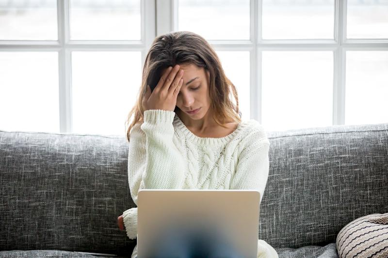 Young woman sitting on couch with laptop in lap, clutching her head
