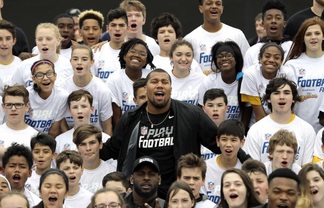 NFL Draft prospect North Carolina State's Bradley Chubb, center, joins participants for a group photograph after a Play Football Clinic Wednesday, April 25, 2018, in Arlington, Texas. The 2018 NFL Draft begins Thursday, April 26, 2018, at AT&T Stadium. (AP Photo/David J. Phillip)