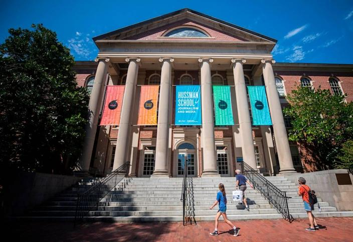 Visitors of UNC-Chapel Hill walk up the steps of Carroll Hall, the building housing the Hussman School of Journalism and Media, in Chapel Hill, N.C. on Wednesday, July 14, 2021.