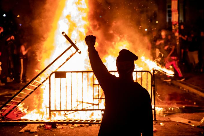A protester raises a fist near a fire during a demonstration outside the White House over the death of George Floyd at the hands of Minneapolis Police in Washington, DC, on May 31, 2020. (Samuel Corum/AFP via Getty Images)