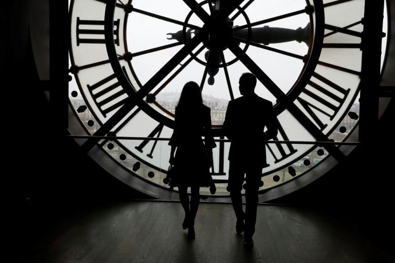 Britain's Prince William and his wife Britain's Kate look across the River Seine at a view of Paris through the clock face at the Musee d'Orsay on March 18, 2017