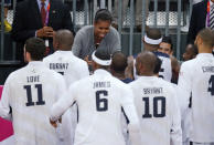 First Lady Michelle Obama congratulates members of Team USA after defeating France in a preliminary men's basketball game at the 2012 Summer Olympics, Sunday, July 29, 2012, in London. (AP Photo/Jae C. Hong)