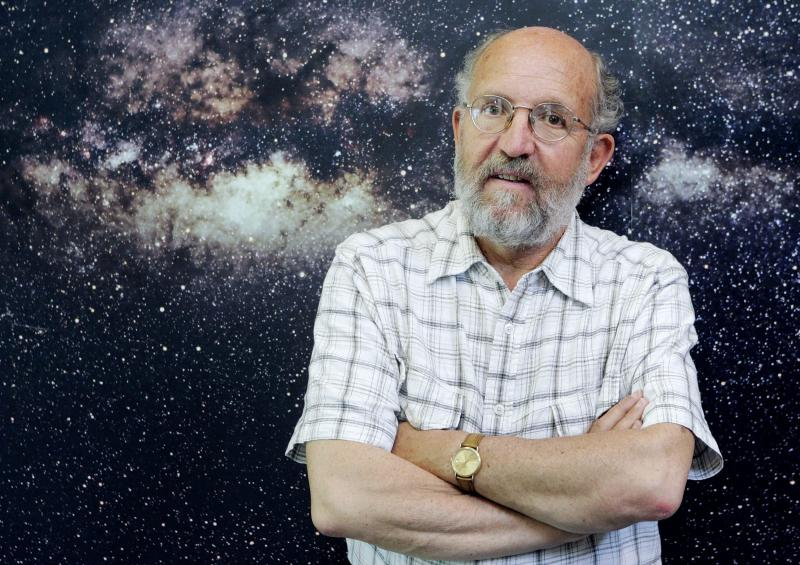 """FILE - In this Wednesday, May 17, 2006 file photo Swiss professor Michel Mayor, astrophysicist and director of the Geneva Observatory, poses in front of the picture of the Milky Way, in Geneva, Switzerland. The 2019 Nobel prize for Physics was given to James Peebles """"for theoretical discoveries in physical cosmology,"""" and the other half jointly to Michel Mayor and Didier Queloz """"for the discovery of an exoplanet orbiting a solar-type star,"""" said Prof. Goran Hansson, secretary-general of the Royal Swedish Academy of Sciences that chooses the laureates. (Salvatore Di Nolfi, Keystone via AP)"""