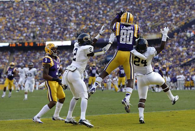 LSU wide receiver Jarvis Landry (80) pulls in a touchdown reception over Kent State cornerback Malcom Pannell (2) and safety Elcee Refuge (24) in the first half of an NCAA college football game in Baton Rouge, La., Saturday, Sept. 14, 2013. (AP Photo/Gerald Herbert)