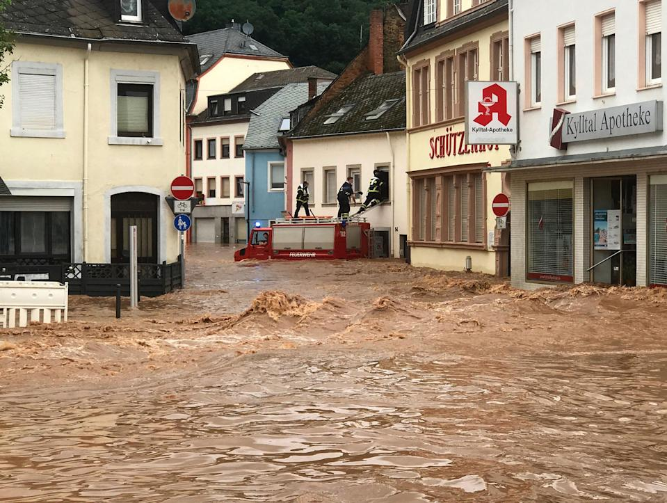 Fire fighters stand atop their vehicle as they climb into a house in the flooded village of Ehrang in Rhineland-Palatinate (Fire Brigades City of Trier/AFP/Getty)