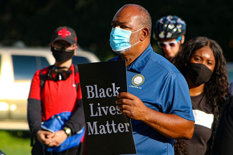 Bishop John Milton of the Lafayette branch of the NAACP holds a sign during a Friday evening protest against police brutality in front of the Louisiana Governor's Mansion in Baton Rouge.