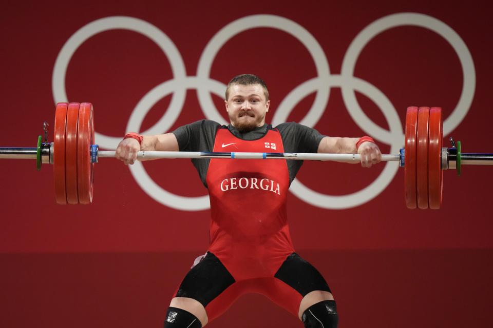Anton Pliesnoi of Georgia competes in the men's 96kg weightlifting event, at the 2020 Summer Olympics, Saturday, July 31, 2021, in Tokyo, Japan. (AP Photo/Luca Bruno)