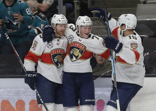 Florida Panthers left wing Dryden Hunt, center, is congratulated by defenseman Mike Matheson, left, and center Riley Sheahan after scoring a goal against the San Jose Sharks during the second period of an NHL hockey game in San Jose, Calif., Thursday, March 14, 2019. (AP Photo/Jeff Chiu)