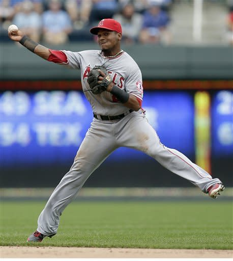 Los Angeles Angels shortstop Erick Aybar throws to first on a single by Kansas City Royals' Jeff Francoeur during the fourth inning of a baseball game on Sunday, Sept. 16, 2012, in Kansas City, Mo. Aybar was charged with a throwing error on the play, advancing Francoeur to second and Billy Butler home to score. (AP Photo/Charlie Riedel)