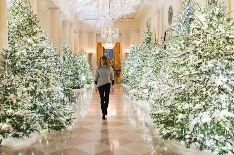 First Lady Melania Trump strolls through a traditionally-decorated White House corridor at Christmas time.