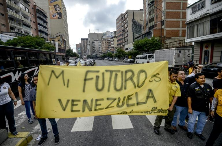 "Venezuelan opposition activists march along a street of Caracas on March 31, 2017 chanting slogans against the government of President Nicolas Maduro and deploying a banner that reads ""My Future Is Venezuela"""