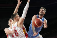 Argentina's Nicolas Laprovittola passes around Spain's Victor Claver, left, during a men's basketball preliminary round game at the 2020 Summer Olympics, Thursday, July 29, 2021, in Saitama, Japan. (AP Photo/Eric Gay)