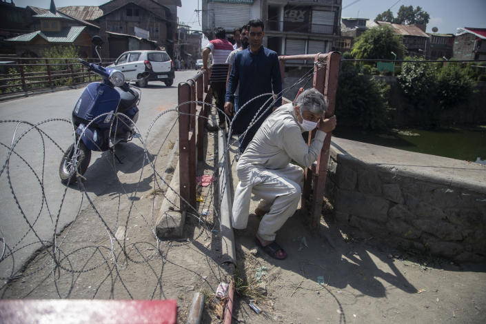 CORRECTS AGE - Kashmiri civilians cross a barricade set up by the police in Srinagar, Indian controlled Kashmir, Thursday, Sept. 2, 2021. Indian authorities cracked down on public movement and imposed a near-total communications blackout Thursday in disputed Kashmir after the death of Syed Ali Geelani, a top separatist leader who became the emblem of the region's defiance against New Delhi. Geelani, who died late Wednesday at age 91, was buried in a quiet funeral organized by authorities under harsh restrictions, his son Naseem Geelani told The Associated Press. He said the family had planned the burial at the main martyrs' graveyard in Srinagar, the region's main city, as per his will but were disallowed by police. (AP Photo/ Mukhtar Khan)