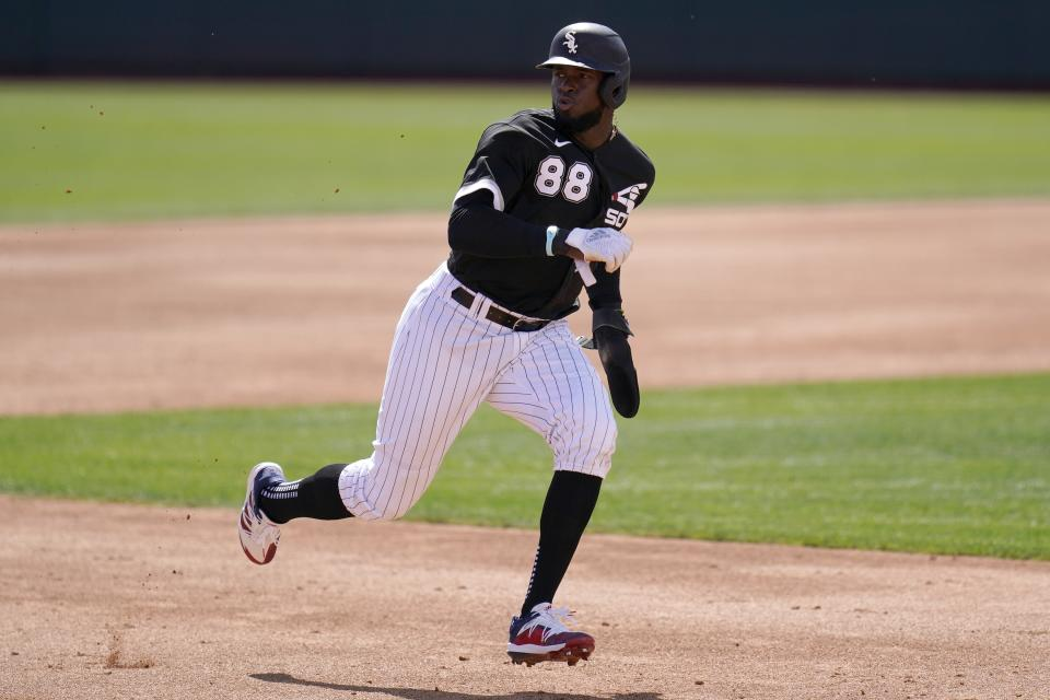 Chicago White Sox's Luis Robert looks for the baseball as he runs to third base on his way to score on a throwing error by Cleveland Indians catcher Austin Hedges during the second inning of a spring training baseball game Saturday, March 20, 2021, in Phoenix. (AP Photo/Ross D. Franklin)