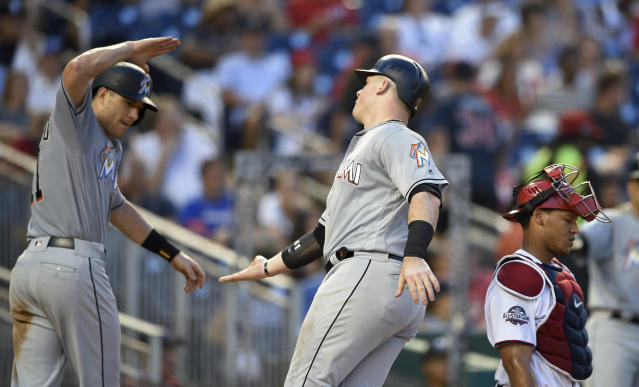 Miami Marlins' Justin Bour, center, celebrates his two-run home run with J.T. Realmuto, left, during the fourth inning of a baseball game, while Washington Nationals catcher Pedro Severino, right, waits Thursday, July 5, 2018, in Washington. (AP Photo/Nick Wass)