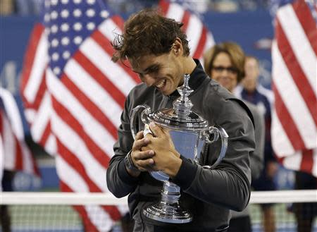 Nadal of Spain embraces his trophy after defeating Djokovic of Serbia in their men's final match at the U.S. Open tennis championships in New York