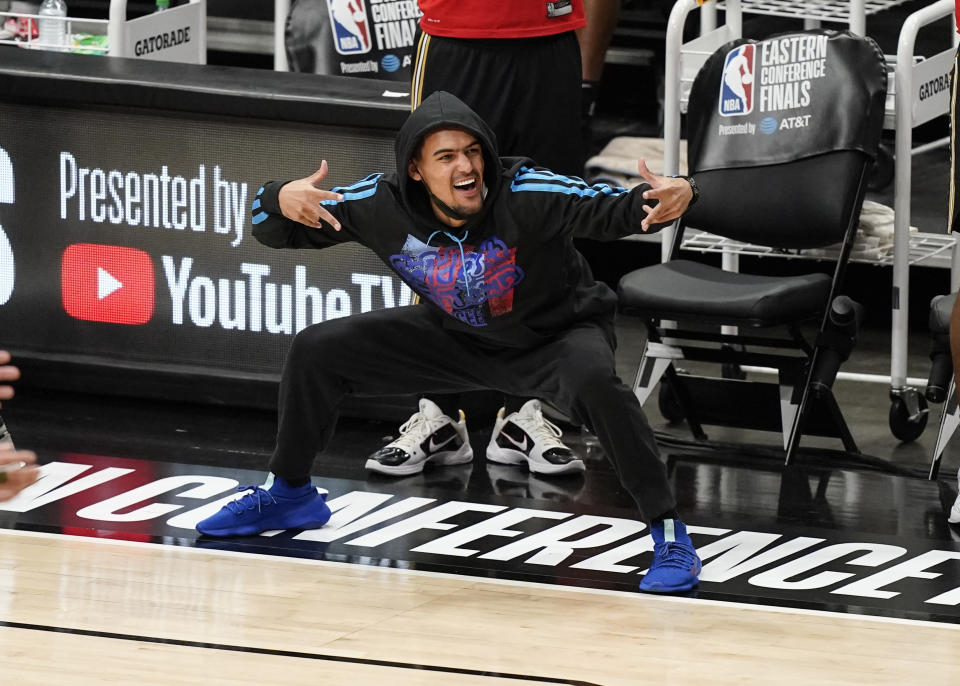 Atlanta Hawks' Trae Young, who did not play, celebrates a score during the second half against the Milwaukee Bucks in Game 4 of the NBA basketball Eastern Conference finals Tuesday, June 29, 2021, in Atlanta. (AP Photo/Brynn Anderson)