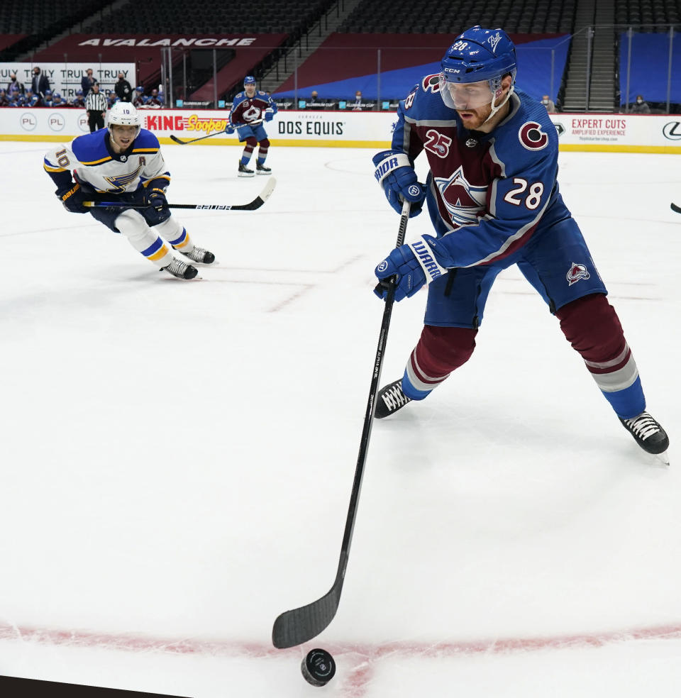 Colorado Avalanche defenseman Ian Cole, front, picks up the puck as St. Louis Blues center Brayden Schenn defends durg the third period of an NHL hockey game Friday, Jan. 15, 2021, in Denver. (AP Photo/David Zalubowski)