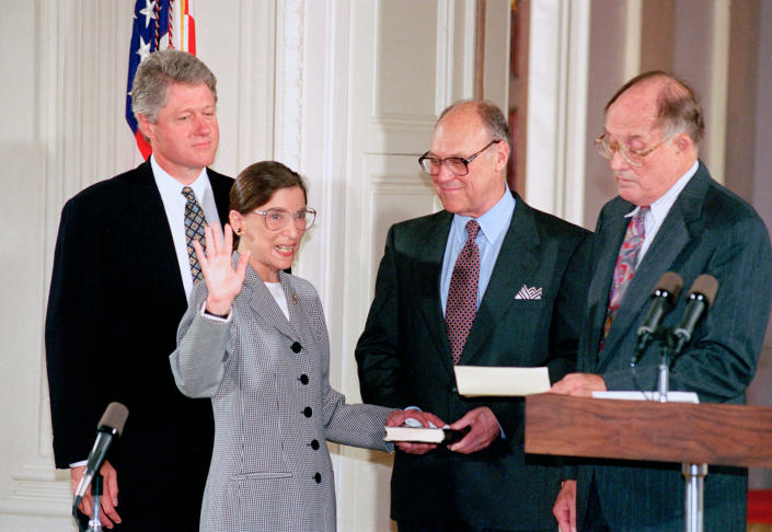 Supreme Court Justice Ruth Bader Ginsburg takes the oath to defend the Constitution. Chief Justice William Rehnquist, right, presides over the ceremony in the East Room of the White House as Ginsburg's husband, Martin, holds the Bible and President Bill Clinton looks on. (Photo: Marcy Nighswander/AP)