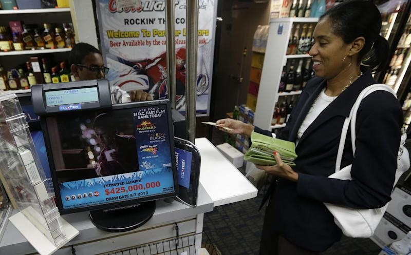 Melina Cholmondeley, right, purchases her Powerball lottery ticket from Harry Singh, left, at Par Mar Liquors in downtown Washington, Tuesday, Aug. 6, 2013. On Tuesday, the Powerball jackpot reached $425 million for Wednesday's drawing. (AP Photo/Pablo Martinez Monsivais)