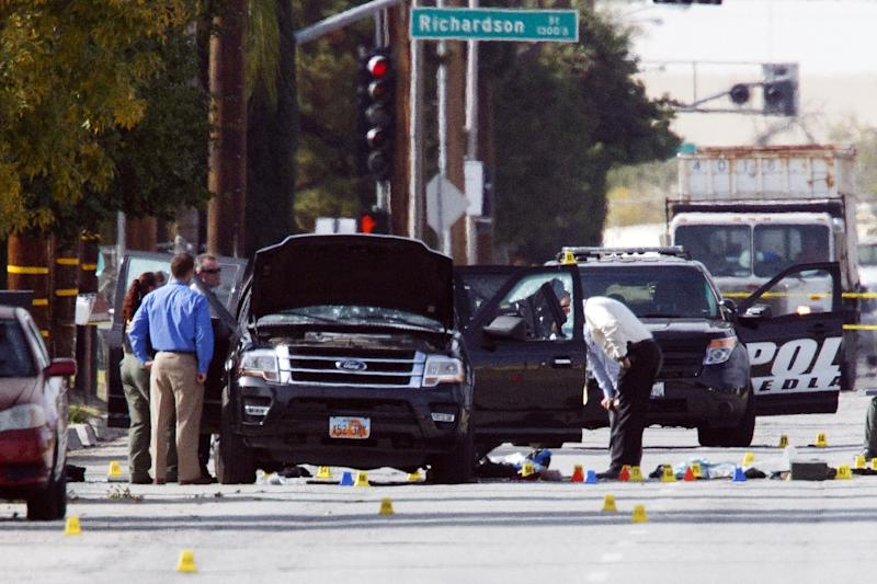 In December 2015, investigators in San Bernardino, California look at the vehicle involved in a shootout between police and two people suspected of killing 14 people after being inspired by radical jihadist ideology (AFP Photo/Patrick T. Fallon)