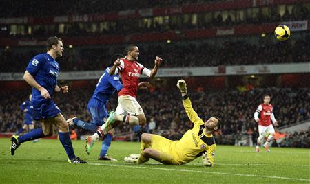 Arsenal's Theo Walcott (2nd R) shoots and scores past Cardiff City goalkeeper David Marshall (R) during their English Premier League soccer match at the Emirates Stadium in London January 1, 2014. REUTERS/Dylan Martinez