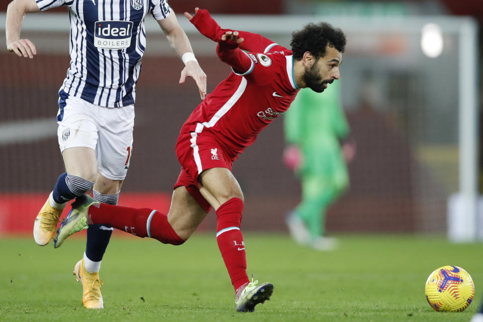 Liverpool's Mohamed Salah chases the ball during an English Premier League soccer match between Liverpool and West Bromwich Albion at the Anfield stadium in Liverpool, England, Sunday Dec. 27, 2020. (Clive Brunskill/Pool via AP)