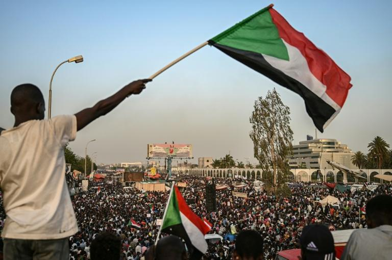 A Sudanese protester waves the national flag during a rally outside the army complex in the capital Khartoum