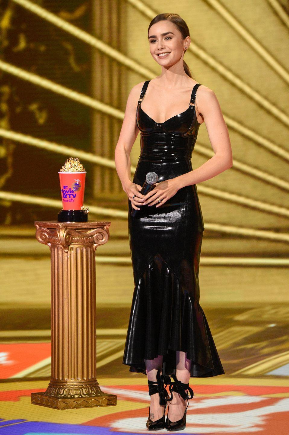 <p><strong>6 December</strong> Lily Collins wore a latex Saint Laurent dress and ribbon-tie heels to present at the MTV Movie Awards 2020. </p>