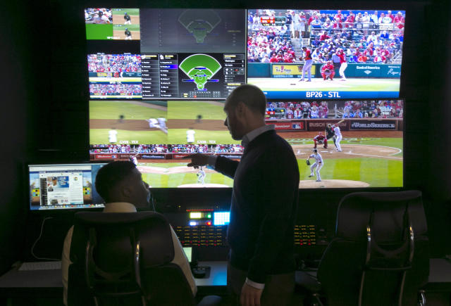 Two technicians work in a booth during a preview of Major League Baseball's Replay Operations Center, in New York, Wednesday, March 26, 2014. Less than a week before most teams open, MLB is working on the unveiling of its new instant replay system, which it hopes will vastly reduce incorrect calls by umpires. (AP Photo/Richard Drew)