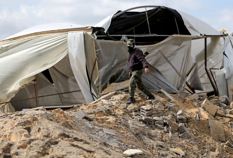 A Palestinian militant walks as he surveys an Islamic Jihad site that was targeted in an Israeli air strike in the southern Gaza Strip
