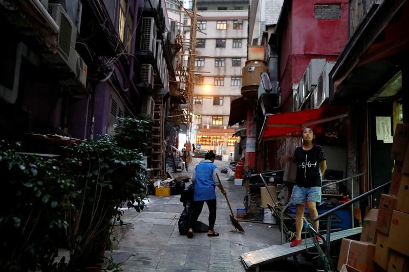 FILE PHOTO: Woman stands outside a shop in an alley in Sheung Wan in Hong Kong