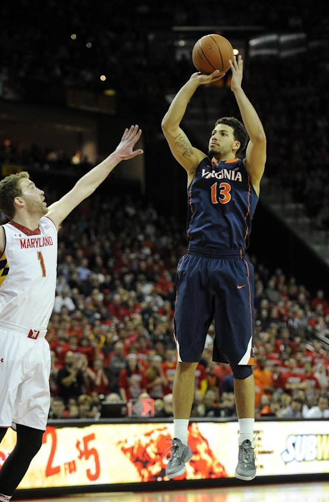 Virginia forward Anthony Gill (13) takes a shot against Maryland forward Evan Smotrycz (1) during the first half of an NCAA college basketball game, Sunday, March 9, 2014, in College Park, Md. (AP Photo/Nick Wass)
