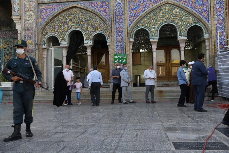 Iranians wait to vote at a polling station during presidential elections in Tehran