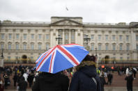 A couple stand under an umbrella will the Union flag on it outside Buckingham Palace in London, a day after the death of Britain's Prince Philip, Saturday, April 10, 2021. Britain's Prince Philip, the irascible and tough-minded husband of Queen Elizabeth II who spent more than seven decades supporting his wife in a role that mostly defined his life, died on Friday. (AP Photo/Alberto Pezzali)
