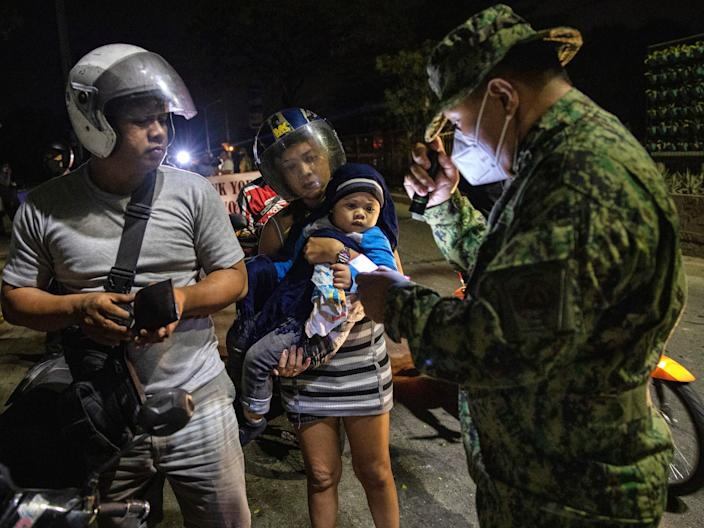 Filipino soldier checks a motorists at a checkpoint as authorities begin implementing a lockdown on Manila on March 15, 2020 in the outskirts of Metro Manila, Philippines.