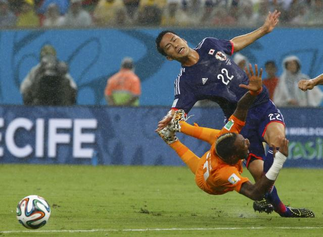 Ivory Coast's Geoffroy Serey Die (L) falls to the ground after being fouled by Japan's Maya Yoshida during their 2014 World Cup Group C soccer match at the Pernambuco arena in Recife, June 14, 2014. REUTERS/Stefano Rellandini (BRAZIL - Tags: SOCCER SPORT WORLD CUP TPX IMAGES OF THE DAY)