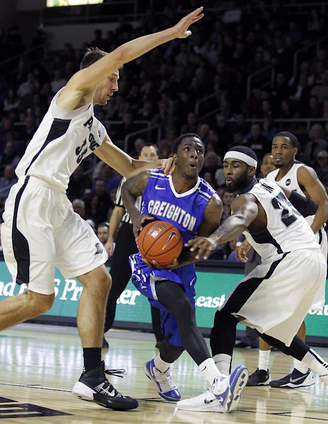 Providence forward Carson Desrosiers, left, and forward LaDontae Henton (23) defend against Creighton guard Devin Brooks, center, during the first half of an NCAA college basketball game on Saturday, Jan. 18, 2014, in Providence, R.I. (AP Photo/Stew Milne)