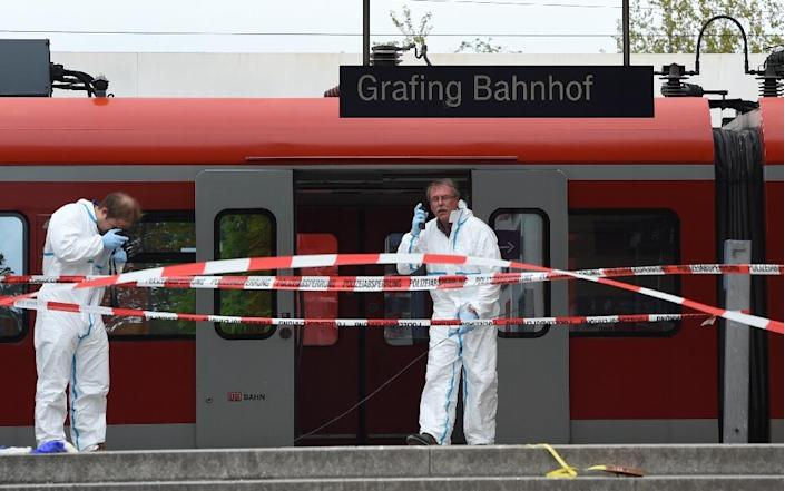 Forensic experts of the police are seen working on a platform at the train station of Grafing, Germany, where a man killed one person and wounded three others in a knife attack on May 10, 2016 (AFP Photo/Christof Stache)