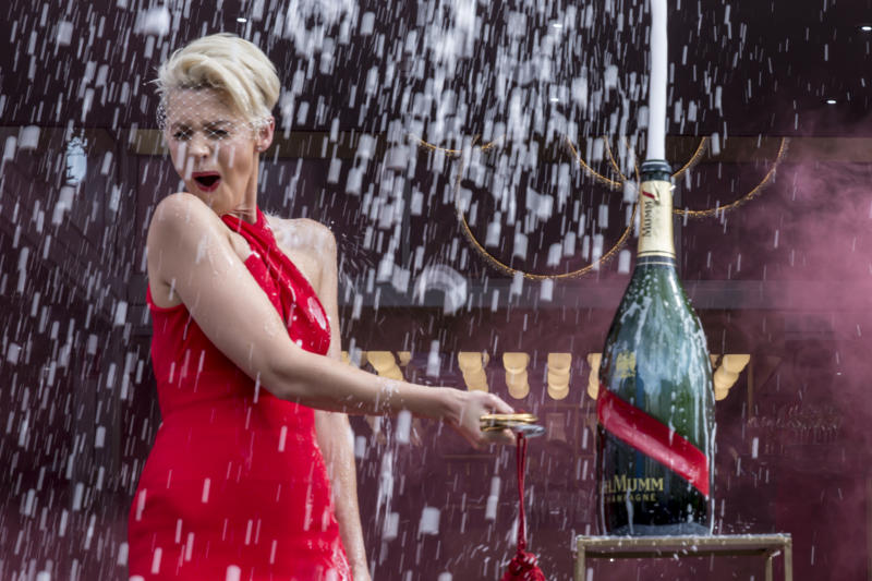 A photo of Kate Peck wearing a red dress and popping a bottle of Mumm champagne during the Birdcage Marquee Preview Day ahead of the Melbourne Cup Carnival on October 31, 2019 in Melbourne, Australia.