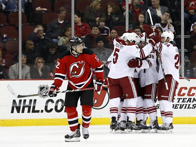 New Jersey Devils ring wing Damien Brunner (12), of the Czech Republic, skates away as members of the Phoenix Coyotes celebrate a goal by Chris Summers during the second period of an NHL hockey game, Thursday, March 27, 2014, in Newark, N.J. (AP Photo/Julio Cortez)