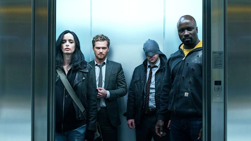 The Defenders riding in an elevator.