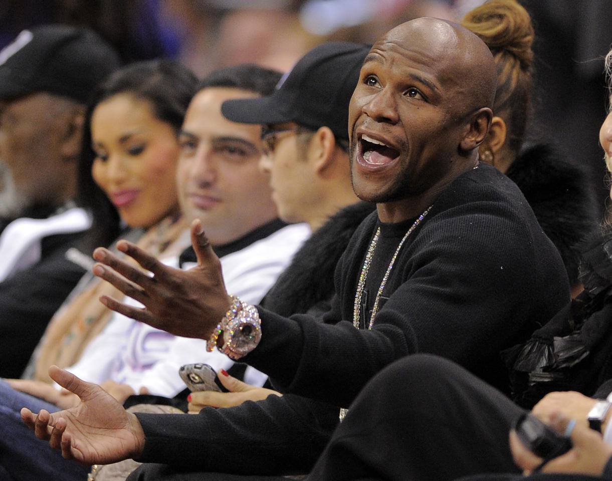 FILE - In this Dec. 30, 2011 file photo, Undefeated boxing champion boxer Floyd Mayweather Jr. talks to a referee as he watches the Los Angeles Clippers' NBA basketball game against the Chicago Bulls, in Los Angeles. Mayweather Jr. has avoided jail time until June 1 in a Las Vegas domestic violence case involving an attack on his ex-girlfriend while two of their children watched in September 2010. (AP Photo/Mark J. Terrill, FIle)