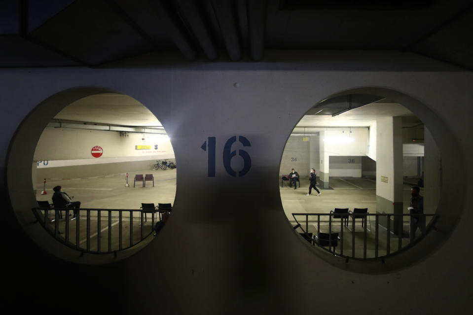 People wait in a converted underground car park vaccination centre in Ebersberg near Munich, Germany, Saturday, May 15, 2021. Hundreds of people have lined up at an improvised vaccination center near Munich to get one of 1,000 doses of the AstraZeneca coronavirus vaccine that were on offer. Police said that around 850 people were standing in line at around 10 a.m. -- and some of them had arrived as early as 5 a.m. (AP Photo/Matthias Schrader)