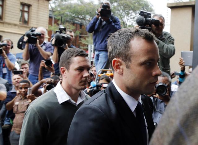 Olympic and Paralympic track star Oscar Pistorius (R) arrives at court ahead of the fourth day of his trial for the murder of his girlfriend Reeva Steenkamp at the North Gauteng High Court in Pretoria, March 6, 2014. REUTERS/Mike Hutchings (SOUTH AFRICA - Tags: SPORT ATHLETICS CRIME LAW)
