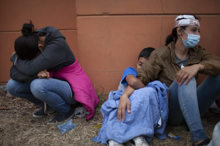 Injured women, part of a Honduran migrant caravan in their bid to reach the U.S. border, weep as they sit on the side of a highway after clashing with Guatemalan police and soldiers in Vado Hondo, Guatemala, Guatemala, Sunday, Jan. 17, 2021. (AP Photo/Sandra Sebastian)