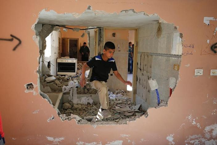 A boy walks through the demolished home of Hussein Abu Ghosh, a Palestinian who stabbed a woman to death in January in the Israeli occupied West Bank (AFP Photo/Abbas Momani)